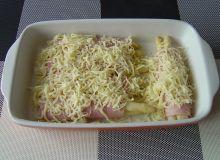 Po dwa sparagi owinąć plasterkiem szynki - ułożyć w naczyniu żaroodpornym i posypać startym serem.